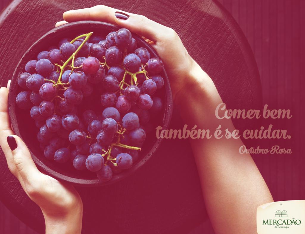 Na imagem, uma mulher segura uma bacia cheia de uvas. Está escrito: comer bem também é se cuidar. Outubro Rosa.
